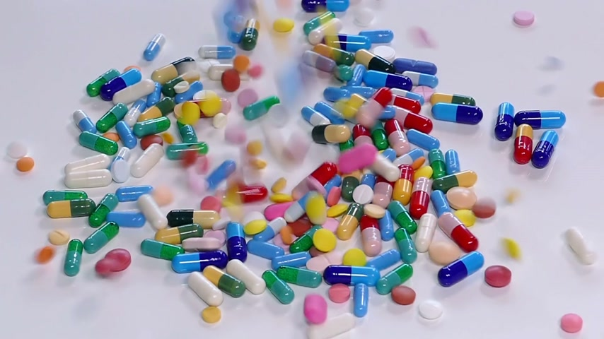 fazla : Colorful pills and drugs falling on white table, concept of medical treatment, slow motion