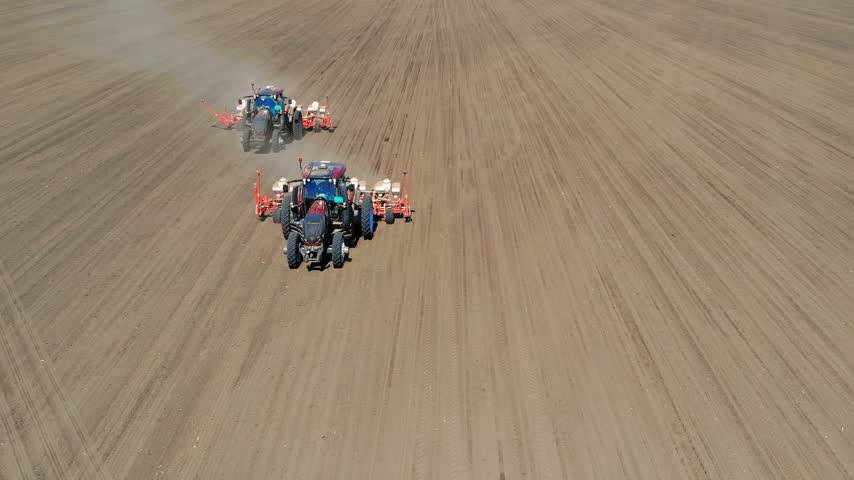 sow : Aerial drone shot of a farmers in two tractors seeding, sowing agricultural crops at field Stock Footage