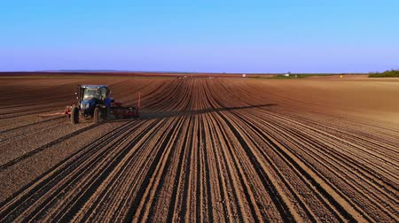 sowing : Drone sliding shot of a farmer in tractor seeding, sowing agricultural crops at field at sunset