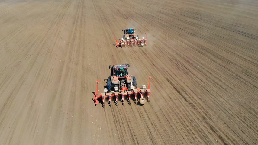 seeder : Aerial drone shot of a farmers in two tractors seeding, sowing agricultural crops at field Stock Footage