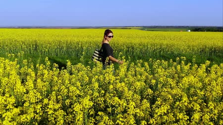 szépen : Aerial drone shot of beautiful woman walks along the country road and enjoys in a yellow oil seed rape flowers field Stock mozgókép