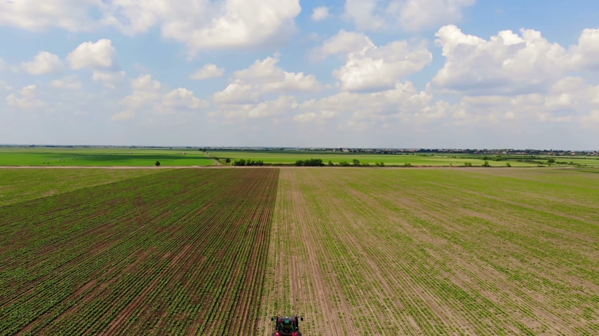 трактор : Aerial drone shot of a farmer in tractor cultivating crops on agricultural field, panoramic view landscape farmland sky with clouds