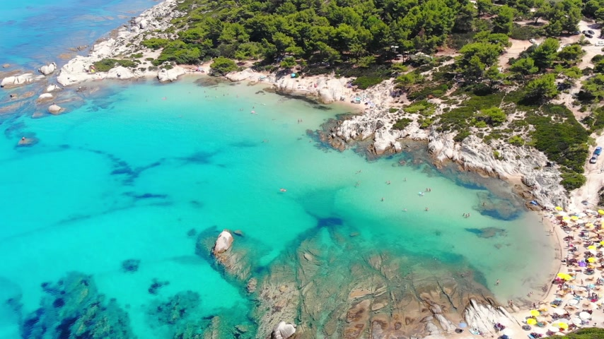 slunečník : Aerial view of beautiful sandy and rocky Orange beach, people sunbathing and swimming. Drone shot flying over amazing famous Orange also called Portokali beach on Sithonia near Sarti, Greece