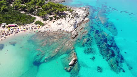 Aerial view of beautiful sandy and rocky Orange beach, people sunbathing and swimming. Drone shot flying over amazing famous Orange also called Portokali beach on Sithonia near Sarti, Greece
