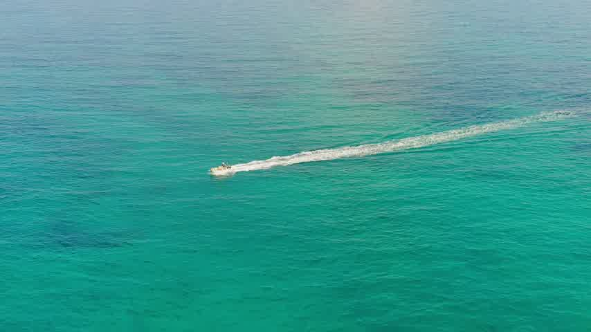 Aerial view of boat moving at high speed on blue sea