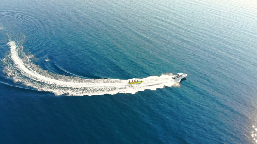 Aerial view of high speed boat pulls the banana boat on blue sea. Drone shot flying over people who enjoy in water sports Stock mozgókép