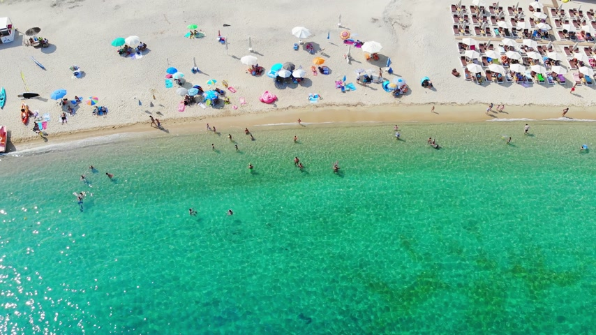 Aerial view of beautiful sandy beach, people sunbathing and swimming. Drone shot flying over Kalamitsi beach in Sithonia, Greece Stock mozgókép