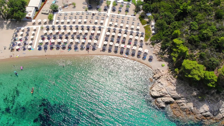 Aerial view of beautiful sandy beach, people sunbathing and swimming. Drone shot flying over Manassu beach in Sithonia, Greece