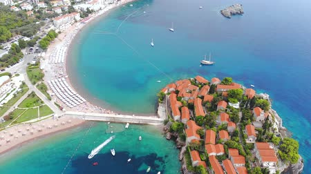 солнечные ванны : Aerial view of St Stephen Island. Flying over Adriatic sea, sunny day. Aerial drone shot, St Stephen Island in Montenegro