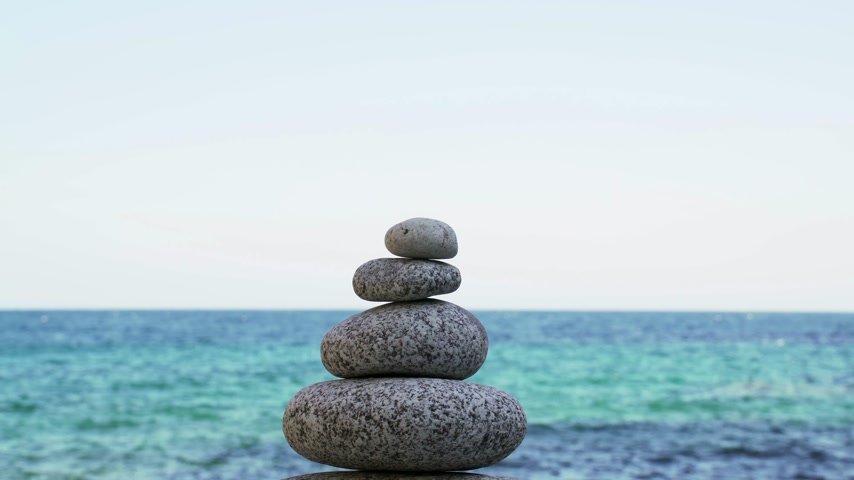 шуй : Stone tower on the beach against the azure sea. Peace and tranquility. Clean blue sky. Soul balance. Cobblestone sculptures.