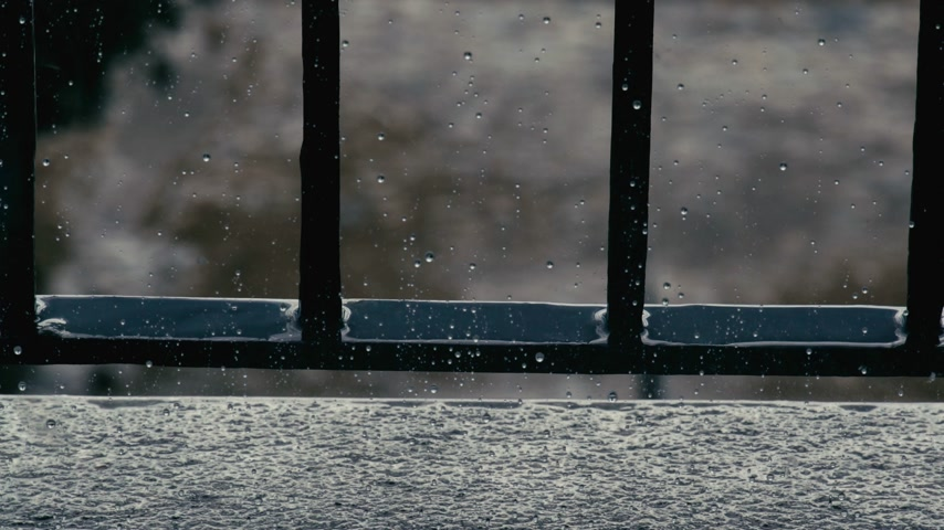pane : Raindrops on a window pane. Severe sea outside the window. Light wave on the surface of the sea. The dramatic sea. Cloudy weather and rain. Calmness and pacification. Stock Footage