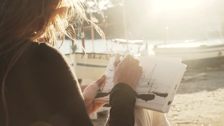 The artist makes sketches on the sunny promenade. Girl draws a coastal landscape with white mediterranean houses. Black and white drawing by liner on white paper. Golden sunlight. Drawing outdoors.