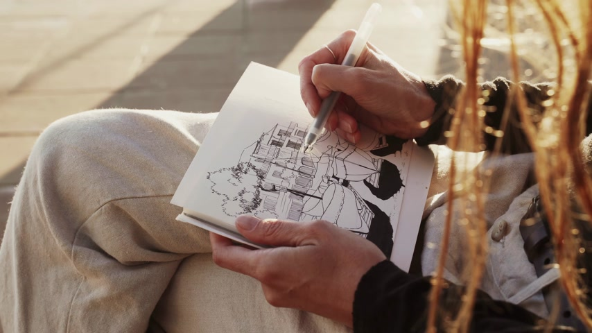 The artist makes sketches on the sunny promenade. Girl draws a coastal landscape with fishing boats. Black and white drawing by liner on white paper. Golden sunlight. Drawing outdoors. Hand drawing.