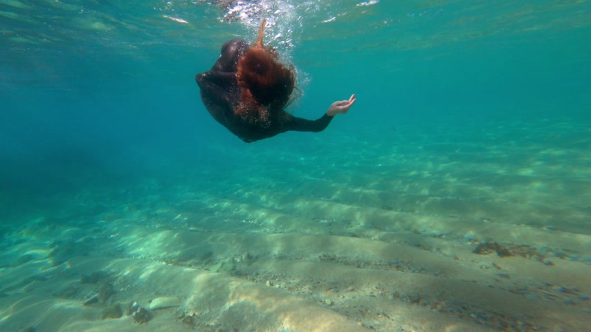 szmaragd : Redhead girl in a black neoprene suit splashes and tumbling underwater. Sun rays in clear emerald water. Spray and sun glare on the sea sand bottom. Swimming in open water. Beautiful underwater. Wideo