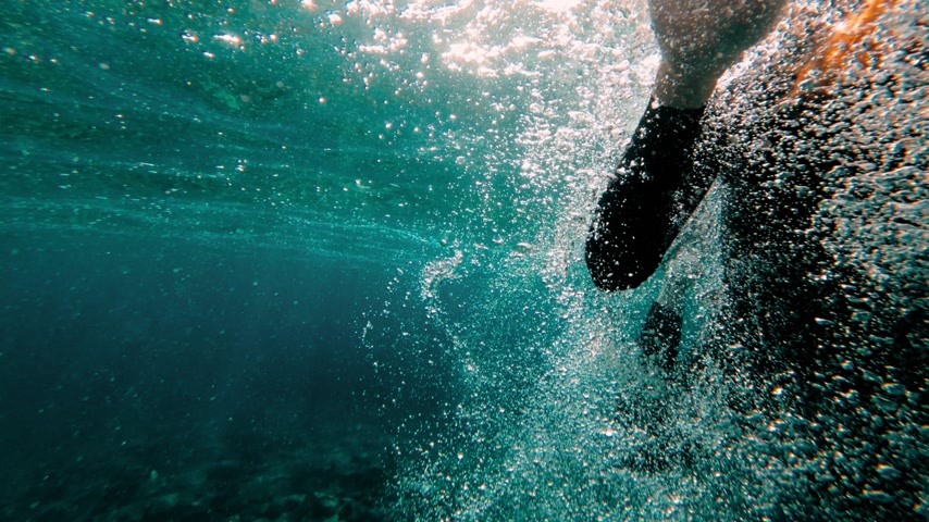 Redhead girl in a black neoprene suit splashes and swims underwater. Sun rays in clear emerald water. Spray and sun glare on the sea sand bottom. Swimming in open water. Beautiful underwater landscape