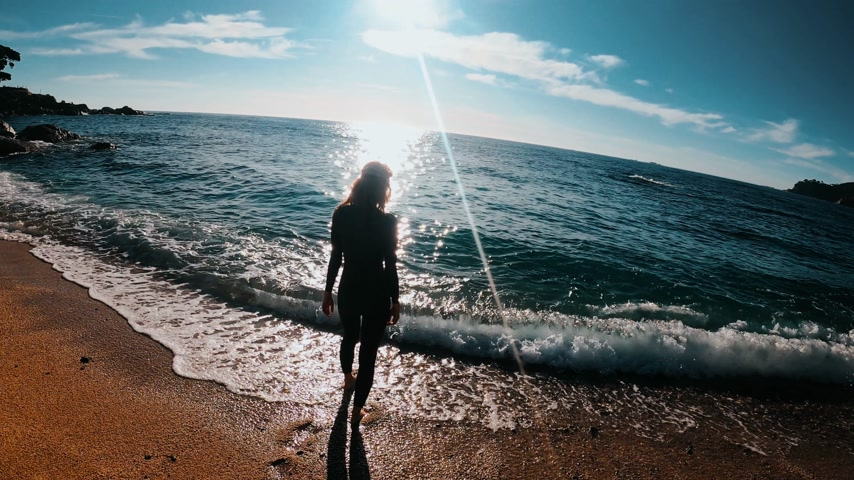 szmaragd : Redhead girl in a black neoprene suit ready to swim and enters the azure water. Sun rays in clear emerald water in beautiful bay. Spray and sun glare. Swimming in open water. Triathlon training. Wideo