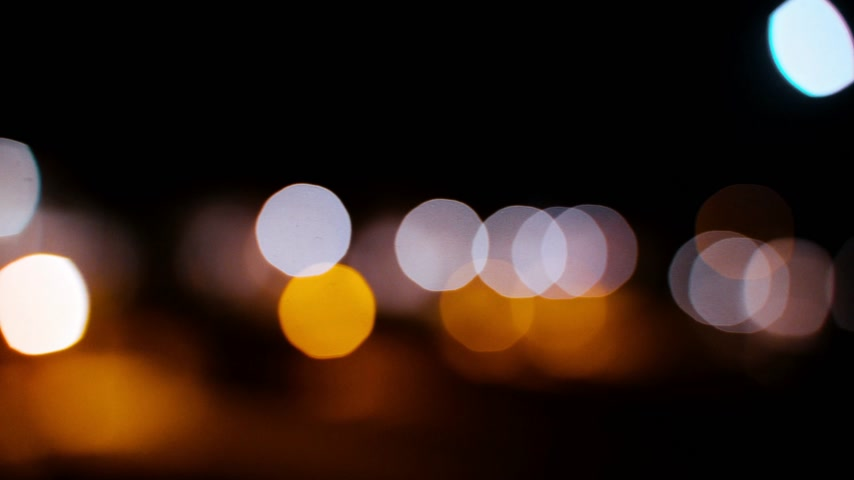 The city dissolves in the evening lights. Nocturne perspective of urban lights. Beautiful yellow, white, orange and rose bokeh light reflections of the night city. Blurred city shine