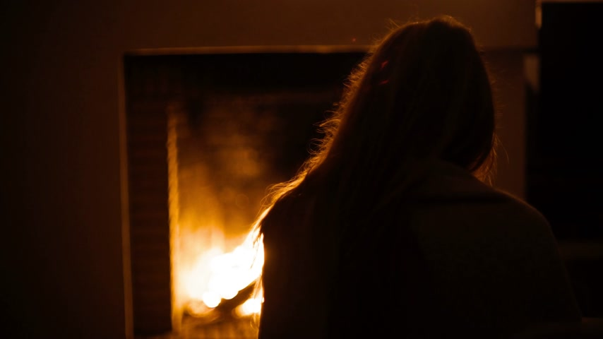 Rear view of a girl sitting in front of a fireplace. A wonderful evening by the burning fireplace. Warmth and comfort. Warm glare from the fire. Relaxing at home. Winter evening by the fireplace. Wideo