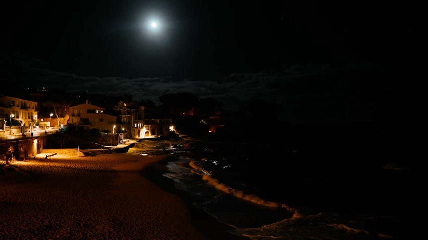 Night view of a small mediterranean fishing village. Fool moon reflection in the water. Night lights on the seashore. Waves splashes in a small bay with a small coastal village. Night sea white houses
