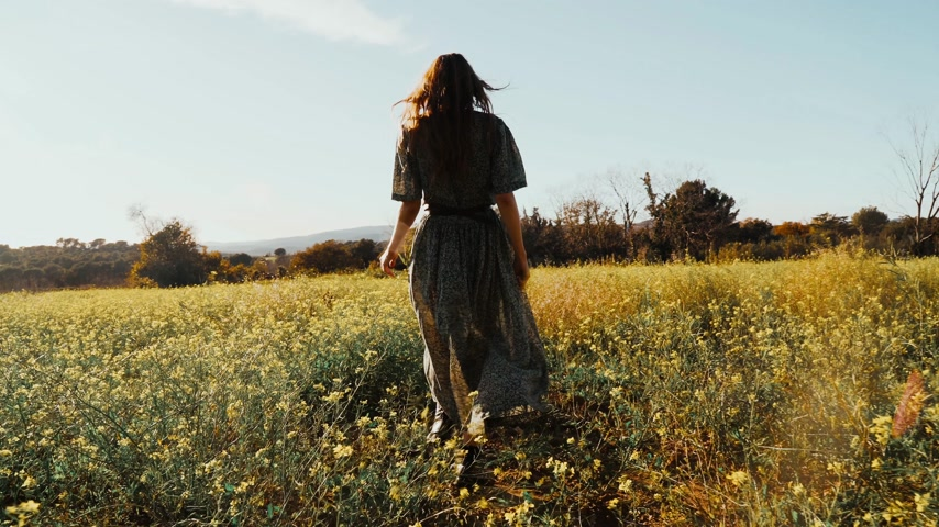 Girl in green dress walks walks through the fields fool of blooming yellow flowers. Long hair woman walks around the beautiful countryside. Golden light in idyllic landscape. Peace and tranquility.