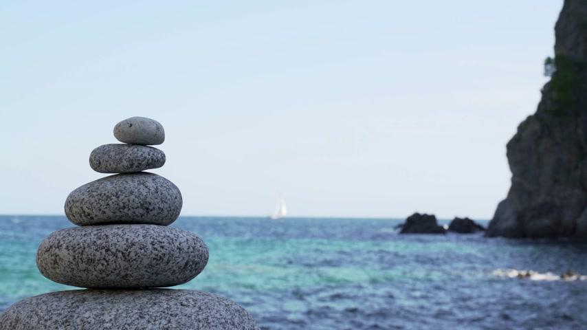 shui : Stone tower on the beach against the azure sea. Beautiful rocks on the background. Peace and tranquility. Clean blue sky. Soul balance. Cobblestone sculptures. Stock Footage