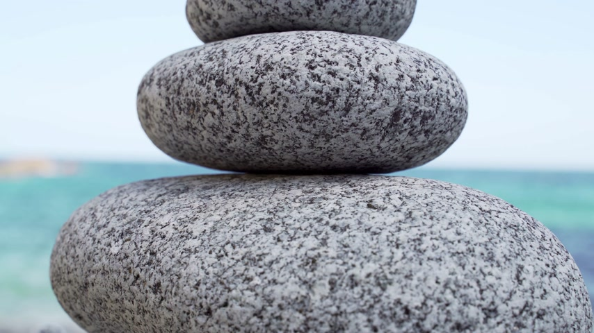 шуй : Stone tower on the beach against the azure sea. Beautiful rocks on the background. Peace and tranquility. Clean blue sky. Soul balance. Cobblestone sculptures. Стоковые видеозаписи