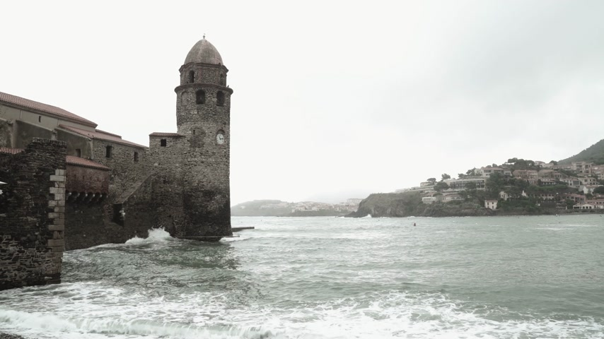 хит : Beautiful waves hit the shore of the small medieval village. Cloudy weather. Swaying sea. Romantic view of a bay. Harsh seascape. Ancient medieval fort with a tower overlooking the sea.