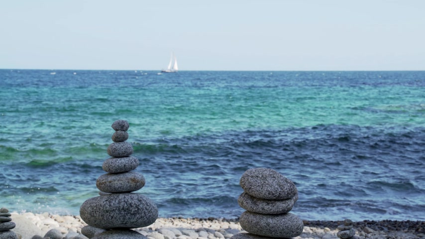 balanceamento : Stone tower on the beach against the azure sea. Beautiful rocks on the background. Peace and tranquility. Clean blue sky. Soul balance. Cobblestone sculptures. Stock Footage