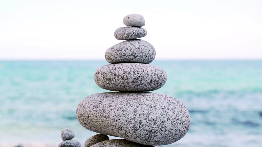 zen como : Stone tower on the beach against the azure sea. Beautiful rocks on the background. Peace and tranquility. Clean blue sky. Soul balance. Cobblestone sculptures. Stock Footage