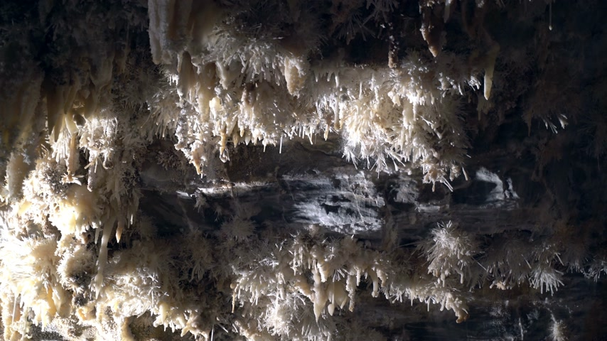 mermer : Beautiful giant cave with mysterious light. Stalactites and stalagmites illuminated by beautiful changing light. Giant grotto underground. Underground Kingdom. Journey to the center of the earth. Stok Video