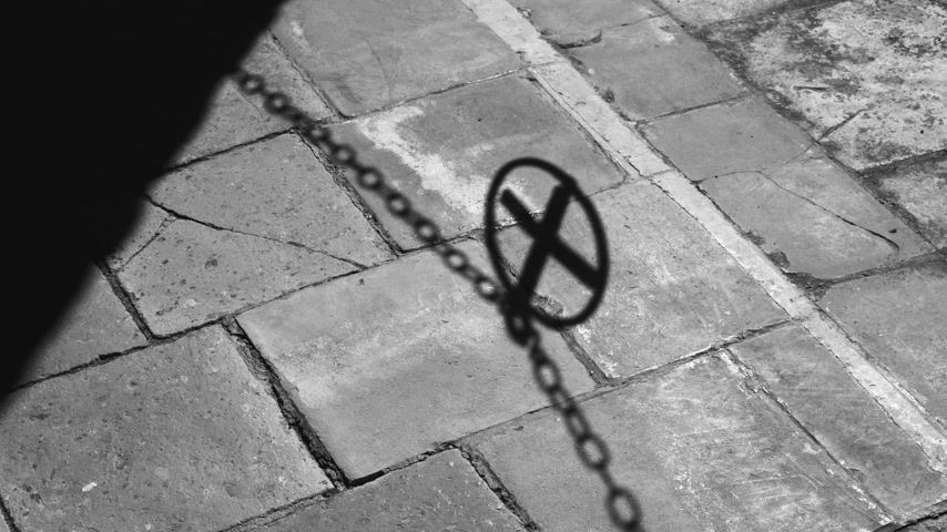passagem : A swinging shadow from a chain fence with a medallion in the shape of a cross. Shadow on the stone pavement. The medieval city. Medieval symbolism.