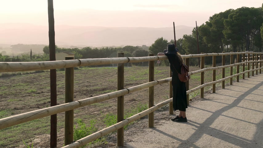 Girl with long hair in black kaftan dress and black hat leans on a fence on a rural road and looks at a beautiful view. Sunny day at countryside. Elegant young woman in black hat. Fashion and beauty.