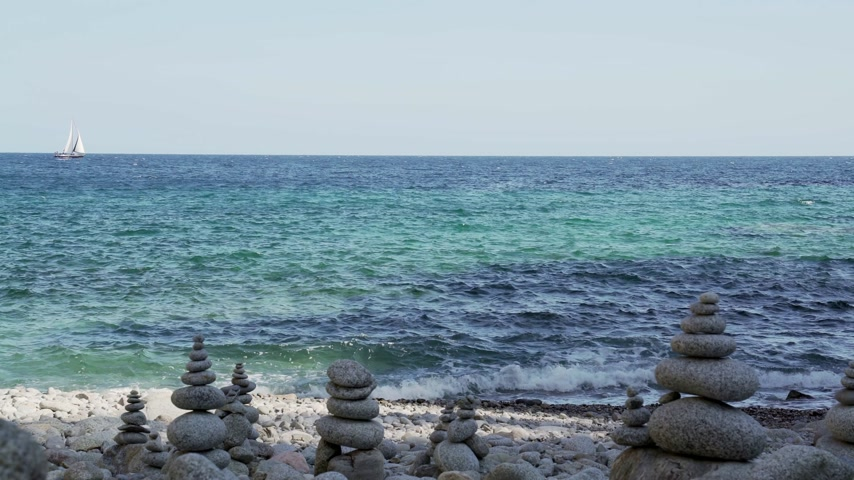 Stone tower on the beach against the azure sea. Beautiful rocks on the background. Peace and tranquility. Clean blue sky. Soul balance. Cobblestone sculptures. Wideo