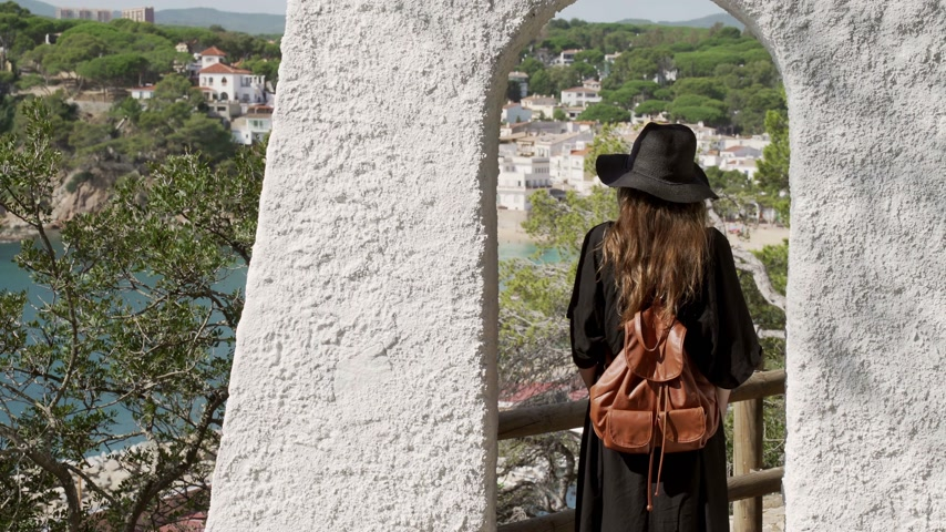 Girl with long hair in black kaftan dress and black hat staying in the white arc over the azure bay. Sunny day, blue sea and pine woods. Elegant young woman in black hat. Fashion and beauty.