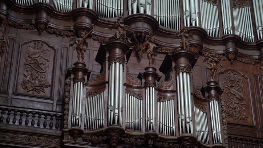 刻まれた : Antique carved wood organ in a catholic temple. Beautiful wood carving. Antiques. Details of a wooden organ and sculpture under the gothic arches of the temple.