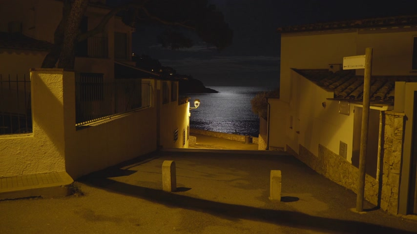 полночь : Moonlight reflected in a sea ripple on the shore of a small Mediterranean village. Full moon. Lunar path in the night sea. Yellow light of a lantern on a quiet street leading to the beach. Moon night.