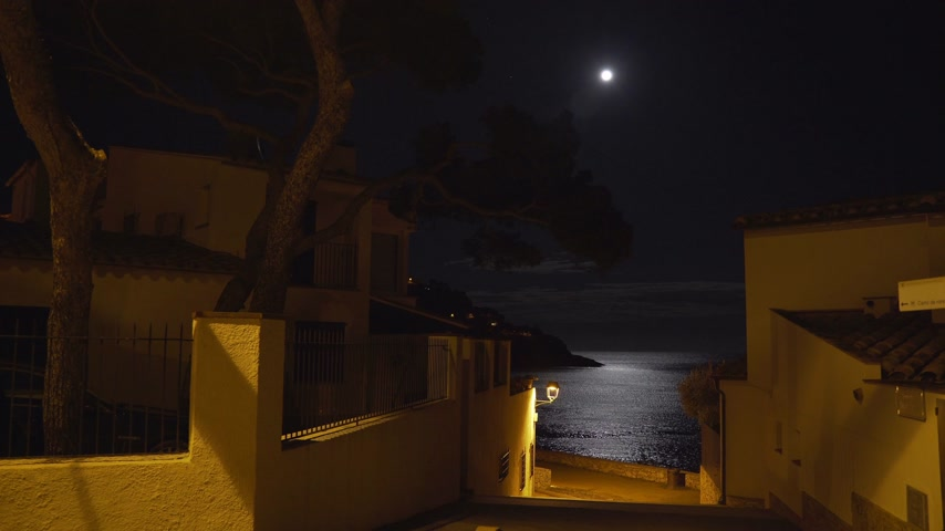 lunar surface : Moonlight reflected in a sea ripple on the shore of a small Mediterranean village. Full moon. Lunar path in the night sea. Yellow light of a lantern on a quiet street leading to the beach. Moon night.