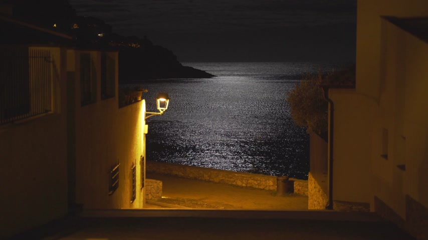 luna : Moonlight reflected in a sea ripple on the shore of a small Mediterranean village. Full moon. Lunar path in the night sea. Yellow light of a lantern on a quiet street leading to the beach. Moon night.