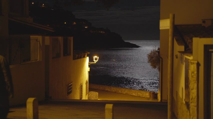 meia noite : Moonlight reflected in a sea ripple on the shore of a small Mediterranean village. Full moon. Lunar path in the night sea. Yellow light of a lantern on a quiet street leading to the beach. Moon night.