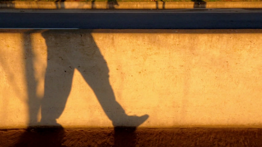Walking man shadow on the concrete fence. Yellow sunlight and contrasting shadows. Walking legs.