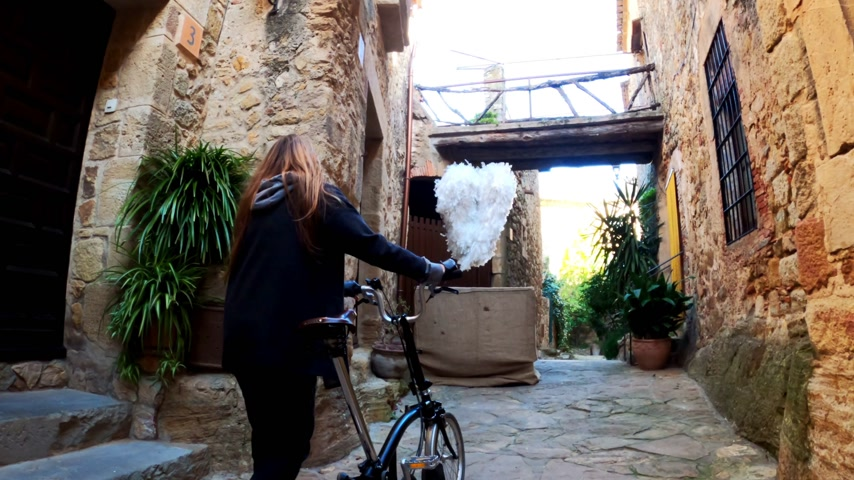 bisikletçi : A girl with long hair walks with a bicycle in the small stone medieval village. Picturesque countryside. Rural bike ride. Old stone street. Golden light. Stok Video