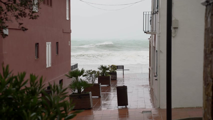 меланхолия : View of the stormy sea from the narrow streets of a small town. Watching the storm. Little village during a storm. Severe raging sea. Big waves. Windy rainy weather. View of the dramatic ocean. Стоковые видеозаписи