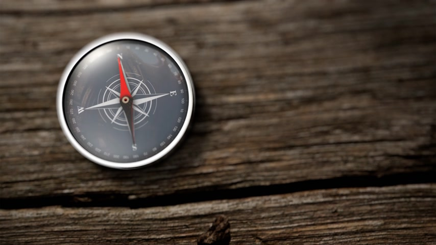 agulhas : Compass with a needle pointing North on a table wooden. Close up view. Objective concept. 3D Rendering Stock Footage
