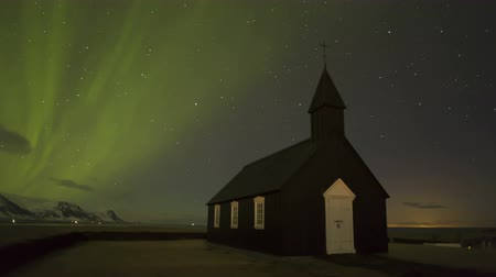 világosság : Black Church of Budir with Northern Lights in Iceland Stock mozgókép