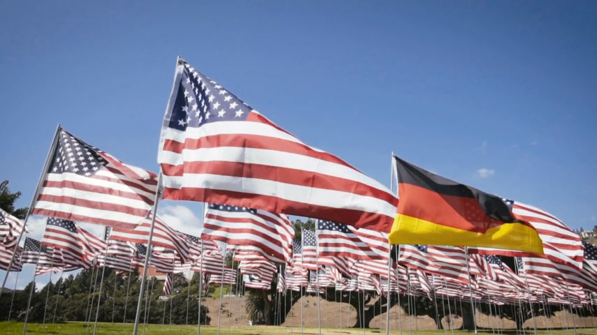 usa independence day : waving german flag in between american flags. diplomatic concept