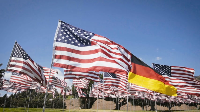 demokratický : slow motion waving german flag in between american flags. diplomatic concept