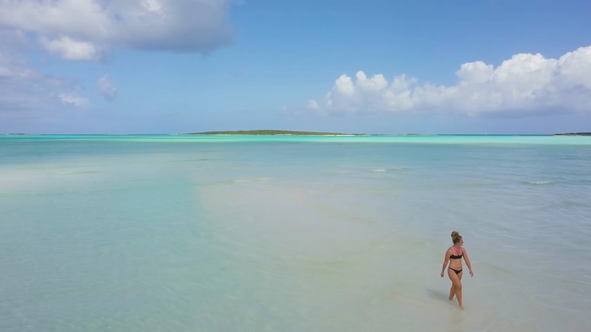 sandy : woman walking on a sandbank at the bahamas.