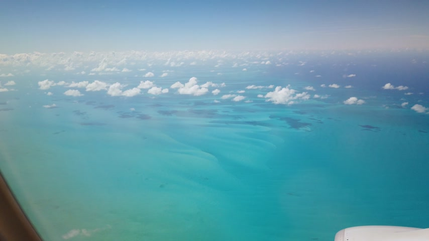 aeroespaço : wing and engine of an airplane flying over bahamas