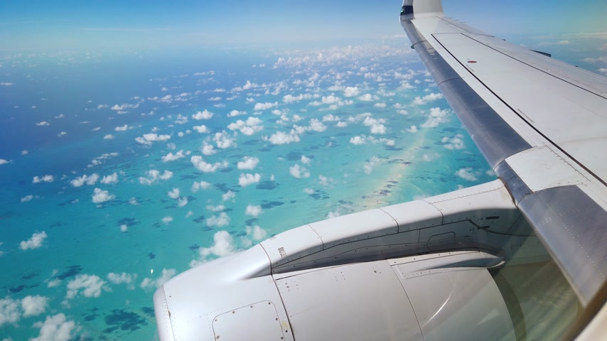 wing and engine of an airplane flying over bahamas