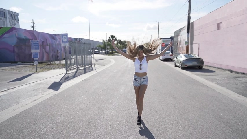 bronzeada : happy young woman walking and spining around. slowmotion